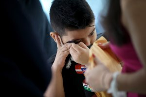 7-year-old Andy wipes tears from his eyes after being reunited with his mother, Arely, at Baltimore-Washington International Airport on July 23, 2018. (Credit: Win McNamee / Getty Images)