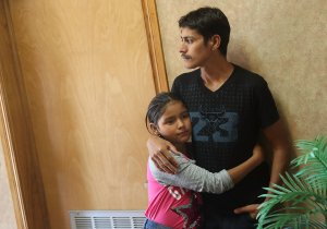 A man, identified only as Leon, spends time with his 11-year-old daughter Anaveli as they are cared for in an Annunciation House facility after they were reunited with each other on July 25, 2018 in El Paso, Texas. (Credit: Joe Raedle / Getty Images)