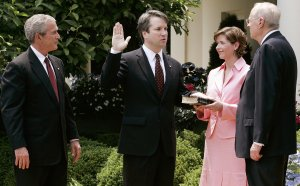 Brett Kavanaugh (second from left) is sworn in by Supreme Court Justice Anthony Kennedy (right) to be a judge at the U.S. Circuit Court of Appeals for the District of Columbia, as his wife Ashley and President George W. Bush look on during a swearing-in ceremony at the White House Rose Garden on June 1, 2006. (Credit: Alex Wong / Getty Images)