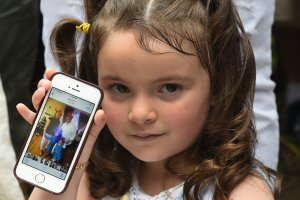 Luciana Villavicencio, the 4-year-old daughter of Pablo Villavicencio, holds up a photo of her family on a cellphone during a press conference in New York on June 18, 2018. (Credit: Timothy A. Clary / AFP / Getty Images)