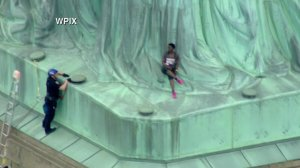 A law enforcement official speaks with a woman who climbed the base of the Statue of Liberty in New York on July 4, 2018. (Credit: WPIX via CNN)