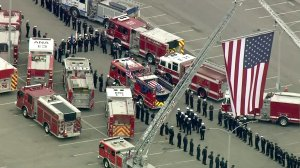 Firefighters line up for a procession for slain Long Beach Fire Department Capt. Dave Rosa on June 3, 2018. (Credit: KTLA)