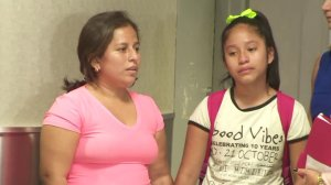 Perla De Velasquez and her daughter, Yoselin, hold hands after a tearful reunion at LAX on July 1, 2018. They had been separated by federal immigration officials for more than a month, according to a lawsuit filed by De Velasquez. (Credit: KTLA)