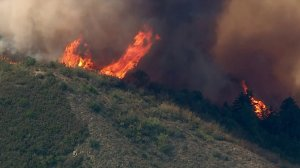 Rising into the sky, flames from the Holy Fire in the Trabuco Canyon area are swept up by winds on Aug. 6, 2018. (Credit: KTLA)