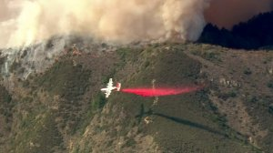 An aircraft drops a stream of retardant over the flames of the fast-moving Holy Fire in the Trabuco Canyon area on Aug. 6, 2018.