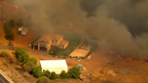 A brush fire inches closer to a home in San Diego County on Aug. 13, 2018. (Credit: KSWB)