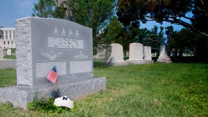"""A flag is placed at the base of the tombstone of U.S. Navy Adm. Charles """"Chuck"""" Larson at the U.S. Naval Academy in Annapolis, Maryland, on Aug. 24, 2018, near where Sen. John McCain will be laid to rest. (Credit: JIM WATSON/AFP/Getty Images)"""