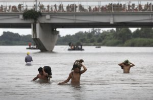 CIUDAD HIDALGO, MEXICO - OCTOBER 20: Immigrants struggle against the current of the Suchiate River while crossing the border from Guatemala into Mexico on October 20, 2018 at Ciudad Hidalgo, Mexico. Many others waited on a bridge to be allowed by Mexican authorities to cross. (Credit John Moore/Getty Images)