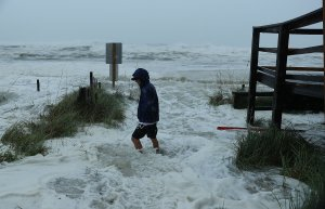 Cameron Sadowski walks along where waves are crashing onto the beach as the outer bands of hurricane Michael arrive on October 10, 2018 in Panama City Beach, Florida. (Credit: Joe Raedle/Getty Images)