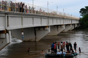 Honduran migrants heading in a caravan to the U.S. await for fellow migrants to jump from the Guatemala-Mexico international border bridge into the Suchiate river, to swim or board a raft to reach Mexico, in Ciudad Hidalgo, Chiapas state, on Oct. 19, 2018. (Credit: Pedro Pardo / AFP / Getty Images)