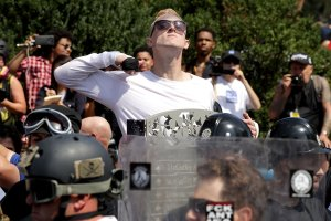"A man makes a slashing motion across his throat toward counter-protesters as he marches with other white nationalists, neo-Nazis and members of the ""alt-right"" during the ""Unite the Right"" rally on Aug. 12, 2017 in Charlottesville, Virginia. (Credit: Chip Somodevilla/Getty Images)"