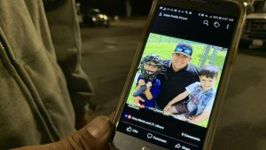 Jason Coffman holds up his phone, showing a photo his 22-year-old son Cody, who died after a gunman opened fire on a bar in Thousand Oaks and killed 12 people on Nov. 7, 2018. (Credit: Kent Nishimura/ Los Angeles Times)