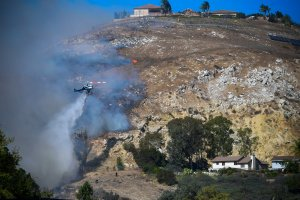 A helicopter drops water over burning embers on a hillside overlooking homes in West Hills, near Malibu on Nov. 11, 2018, as the battle to control the Woolsey Fire continued. (Credit: Frederic J. Brown/AFP/Getty Images)