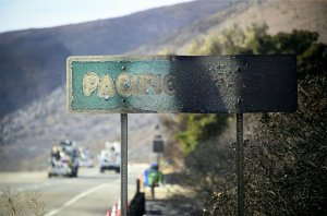 A fire-damaged Pacific Coast sign remains standing along the Pacific Coast Highway amid the blackened and charred hills from the Woolsey Fire in Malibu on Nov. 15, 2018. (Credit: Frederic J. Brown / AFP / Getty Images)