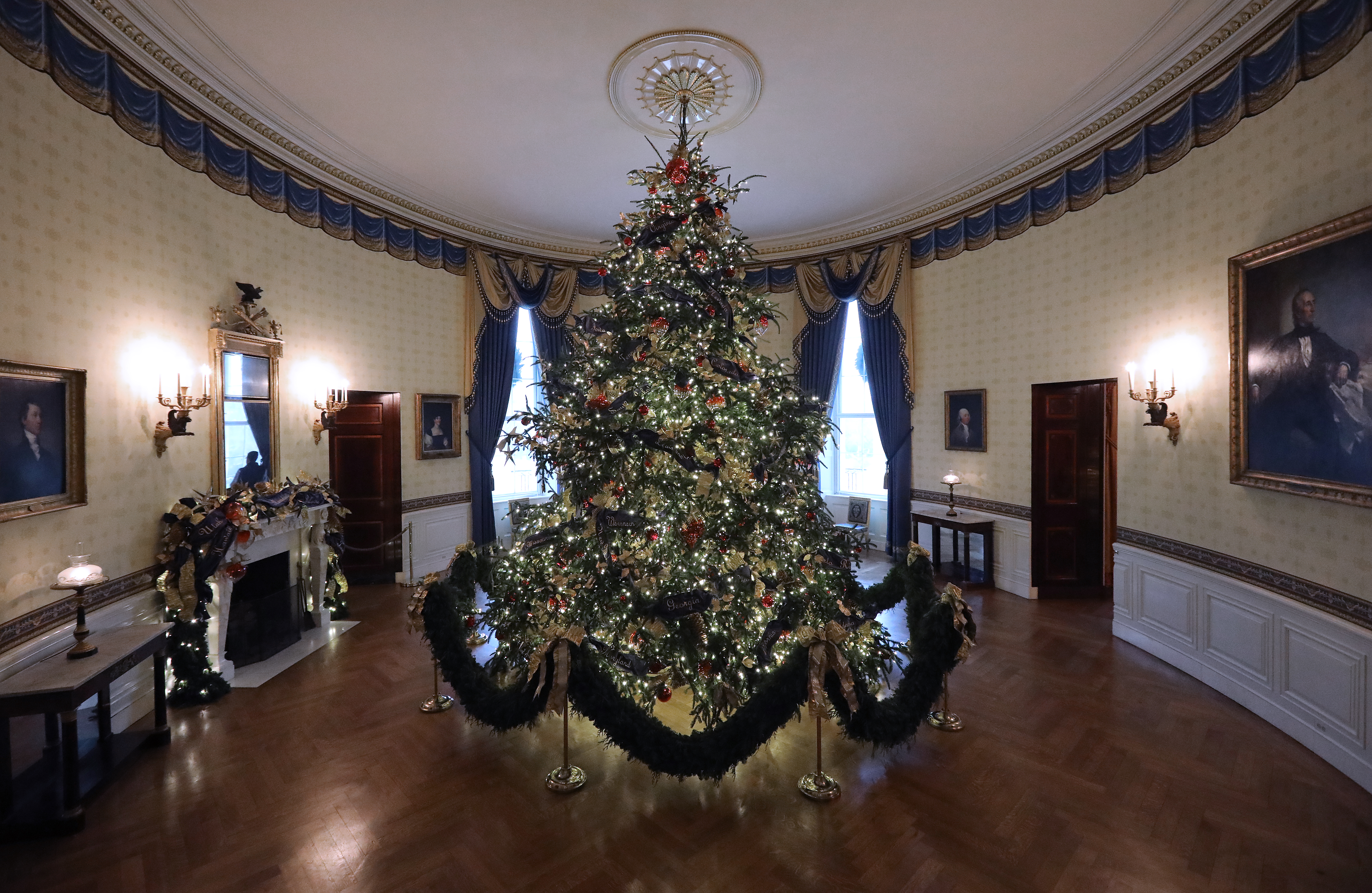 At 18 feet tall, the official White House Christmas is dressed in over 500 feet of blue velvet ribbon embroidered in gold with each state and territory, on display inside the Blue Room at the White House November 26, 2018 in Washington, DC. (Credit: Chip Somodevilla/Getty Images)