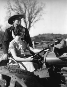 """American actors Richard Arlen and Mary Brian ride a tractor on the Paramount Ranch during the filming of """"Gun Smoke,"""" circa 1931. (Credit: Hulton Archive/Getty Images)"""