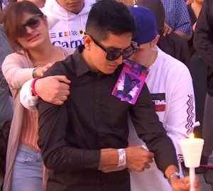 A photo of 3-year-old Nathan Luna, who was killed at his Fontana home on Nov. 1, 2018, sits on the shoulder of a man tearfully grieving the child's death during a vigil the following day. (Credit: RMG News)