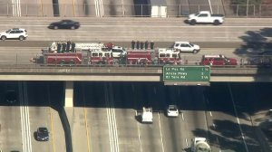 Fire trucks line a freeway overpass during a procession for Costa Mesa Fire and Rescue Capt. Mike Kreza from Mission Viejo to Santa Ana on Nov. 5, 2018. (Credit: KTLA)