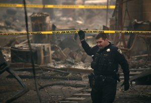 A Paradise police officer walks under crime scene tape that blocks off an area where human remains were found in a car that was destroyed by the Camp Fire on Nov. 15, 2018, in Paradise. (Credit: Justin Sullivan / Getty Images)