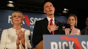 Florida Gov. Rick Scott speaks as he stands with his wife, Ann Scott (left), and daughter Alison Guimard (right) during his election night party on Nov. 6, 2018, in Naples, Florida. (Credit: Joe Raedle/Getty Images)