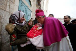 Latin Patriarch of Jerusalem Pierbattista Pizzaballa greets a Muslim Palestinian woman and a baby in the West Bank city of Bethlehem, on Dec. 24, 2018. (Credit: HAZEM BADER/AFP/Getty Images)