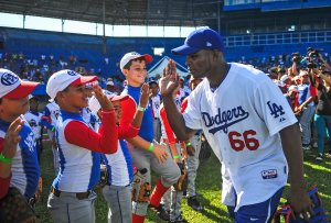 Cuban MLB player Yasiel Puig high fives Cuban children at the Latin American Stadium in Havana on Dec. 16, 2015. (Credit: Yamil Lage / AFP / Getty Images)