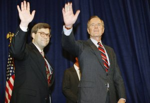 In this Nov. 26, 1991, file photo, President George H.W Bush, right, and William Barr wave after Barr was sworn in as the new Attorney General of the United States at a Justice Department ceremony in Washington. (Credit: Scott Applewhite / AP via CNN)