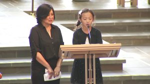 Mai, the wife of late KTLA anchor and reporter Chris Burrous, stands alongside their daughter, 9-year-old Isabella, as she addresses mourners during a memorial service in Whittier on Jan. 11, 2019. (Credit: KTLA)