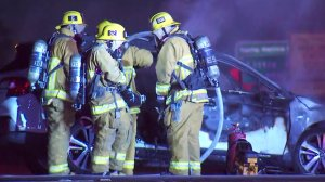 Los Angeles Fire Department officers at the scene where a vehicle was charred black after catching fire on the 101 Freeway on Jan. 28, 2019.