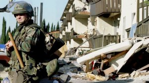 A National Guardsman stands guard outside the ruins of the Northridge Meadows Apartments where 16 people died during the 17 January 1994 earthquake that rocked Southern California. (Credit: TIM CLARY/AFP/Getty Images)