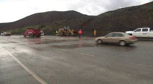 Caltrans crews work to cleanup debris along Pacific Coast Highway during a winter storm on Jan. 14, 2019. (Credit: KTLA)