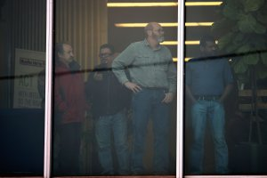 Workers look out an office window following a shooting at the Henry Pratt Co. plant in Aurora, Illinois, on Feb. 15, 2019. (Credit: Scott Olson / Getty Images)