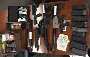 Firearms and counterfeit cash are seen in this photo from the Ventura County Sheriff's Office.