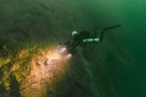 Divers look for fossils embedded in a cenote wall in Belize on Feb. 27, 2019. (Credit: Tony Rath/VOPA via CNN)