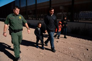 A family from El Salvador walks with a Border Patrol agent after crossing the Rio Grande to claim asylum in El Paso, Texas, on March 19, 2019. (Credit: Paul Ratje / AFP / Getty Images)
