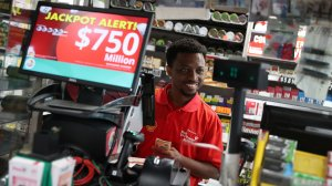 Jackson Mauvais sells Powerball tickets to a customer at the Shell Gateway store on March 26, 2019 in Boynton Beach, Florida. (Credit: Joe Raedle/Getty Images)