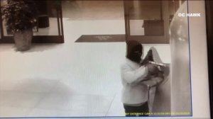 An armed robber is seen pointing a gun in a hotel in Irvine in this surveillance footage. (Credit: OC Hawk)