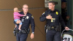 Parishioners and police tackled a woman who entered a Clairemont church service carrying a baby and a handgun on Easter Sunday. (Credit: KSWB via CNN Wire)