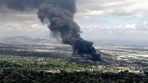A massive plume of black smoke rises from a fire at a recycling facility in Ontario on April 30, 2019. (Credit: KTLA)