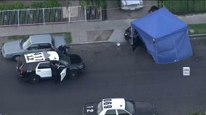 Police investigate a shooting that left a woman and a girl wounded near 60th and Hoover streets in South Los Angeles on April 26, 2019. (Credit: KTLA)