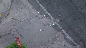 Police evidence markers sit at the corner of 63rd and Hoover streets in South Los Angeles following a shooting that left a woman dead and a 10-year-old girl wounded. (Credit: KTLA)