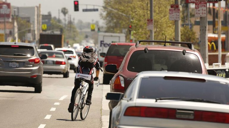 A cyclist rides next to a lane of parked cars on Manchester Avenue in South Los Angeles, one of the deadliest streets in the city for pedestrians and cyclists. Upgrades to Manchester were among hundreds made during the first 3½ years of Vision Zero, an initiative by Mayor Eric Garcetti to eliminate traffic deaths on L.A. streets by 2025. But rather than decline, fatal car crashes have risen 32% since 2015, the year Vision Zero began. In that time, more people have died in traffic collisions — 932 — than were shot to death in the city, according to coroner's data. (Credit: Al Seib / Los Angeles Times)