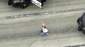 A woman, later identified by police as Alison Hart of Redondo Beach, surrenders to authorities following a pursuit that ended in a shootout in Vernon on May 10, 2019. (Credit: Sky5)