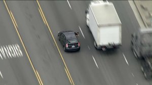 A person is seen pointing a gun at pursuing officers during a chase on May 10, 2019 in Vernon. (Credit: KTLA)