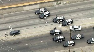 Police cars surround a vehicle after a pursuit on May 10, 2019 in Vernon. (Credit: KTLA)