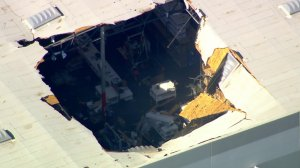 A large is is visible in the roof of a building after an F-16 pilot ejected just before a crash near March Air Reserve Base in Riverside County on May 16, 2019. (Credit: KTLA)