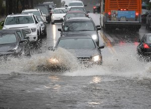 Cars drive through a flooded street after a storm dumped heavy rain on Los Angeles on February 2, 2019, (Credit: MARK RALSTON/AFP/Getty Images)