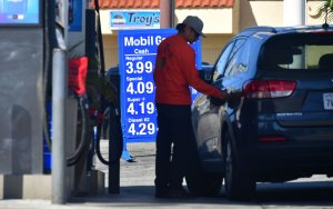 A driver closes the cap on his tank after filling up at a Los Angeles gas station on April 9, 2019. (Credit: Frederic J. Brown / AFP / Getty Images)