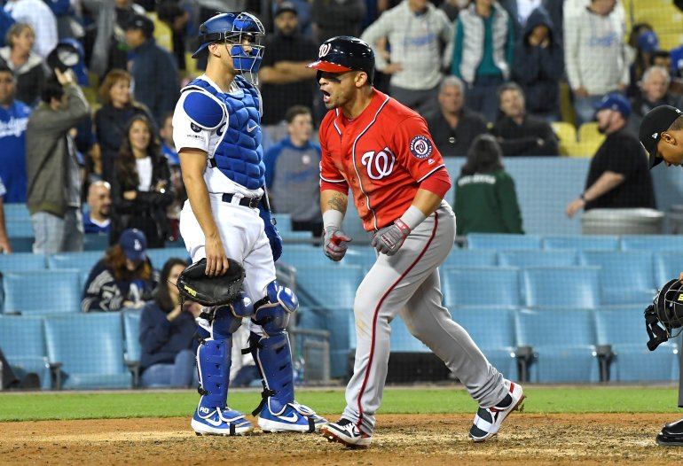 Austin Barnes #15 of the Los Angeles Dodgers looks on as Gerardo Parra #88 of the Washington Nationals celebrates as he crosses the plate after hitting a grand slam home run off Dylan Floro in the eighth inning of the game at Dodger Stadium on May 11, 2019. (Credit: Jayne Kamin-Oncea/Getty Images)