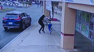 A man is seen on surveillance video snatching the purse of a woman who was later dragged by the suspects' vehicle in Garden Grove on May 8, 2019.